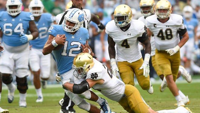 North Carolina Tar Heels quarterback Chazz Surratt (12) is tackled by Notre Dame Fighting Irish linebacker Drue Tranquill (23) in the second quarter at Kenan Memorial Stadium.