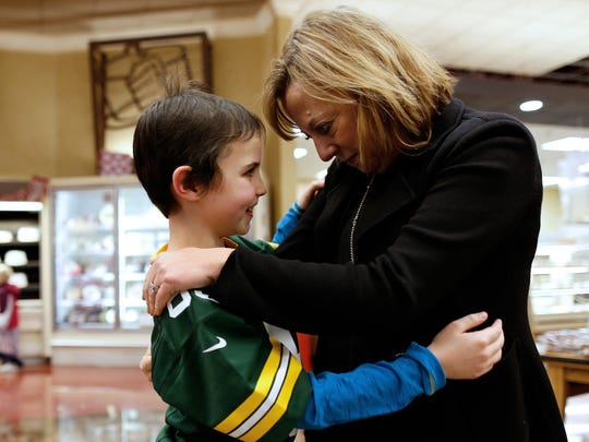 Pamela Henson, Regional President Gannett Wisconsin Media, embraces Make-A-Wish child Maggie Hendrick, 8, who created a holiday greeting card with Green Bay Packers wide receiver James Jones (back left) to raise almost $10,000 for the Children's Hospital of Wisconsin and Make-A-Wish Wisconsin combined. One of the checks for $4721.50 was presented to Make-A-Wish Wisconsin on Tuesday, Jan. 5, 2016 at the Copps off of Lime Kiln road, one of the locations the card was sold.