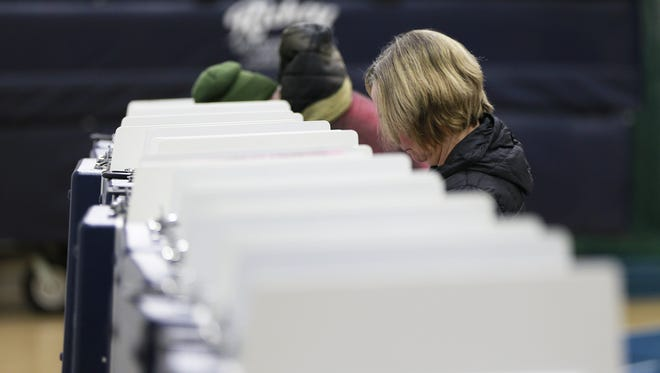 Voters' heads can be seen above the voting booths as they work on their ballots Tuesday morning, April 3, 2018, at Wausau West High School gym in Wausau.