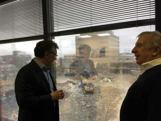 Don Sinex, left, and Nick Principe watch the demolition of the Burlington Town Center site from Sinex's office on Thursday, April 26, 2018.