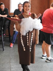 Kayla Hysong in costume passed out cupcake samples for Coshocton Coffee Connections grand opening this week.