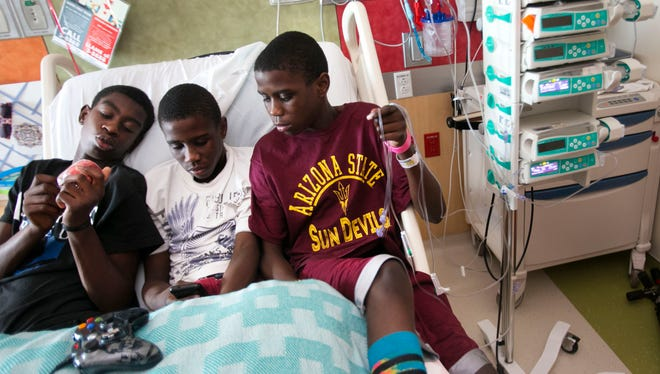 The Buchanan brothers of Chandler, Ariz., (from left) Jonathan, 14, and twins Joshua, and Jordan, 16, hang out together in Jordan's bed at Phoenix Children's Hospital on Saturday, Aug. 31, 2013.