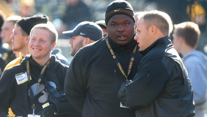 North Fayette Valley's Juan Harris, an Iowa commit, stands on the sidelines with Iowa recruiting coordinator Seth Wallace prior to the Hawkeyes' game against Indiana at Kinnick Stadium on Monday, Oct. 13, 2014.  David Scrivner / Iowa City Press-Citizen