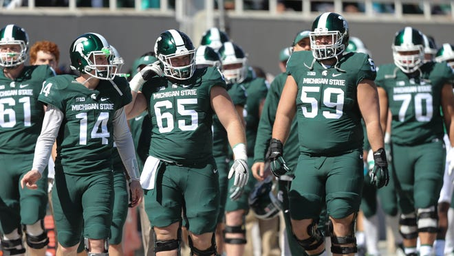 Michigan State quarterback Brian Lewerke (14) and offensive linemen Brian Allen (65) and David Beedle (59) take the field for the spring game at Spartan Stadium, Saturday, April 1, 2017.