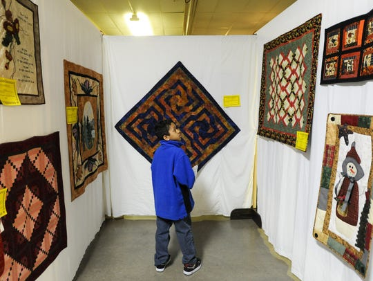 Noah Carle looks for details on quilts in a scavenger