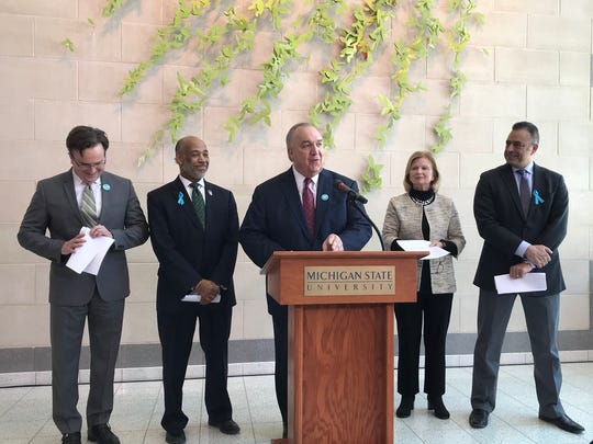 Michigan State Interim President John Engler, center, speaks during a press conference on Wednesday in the Janice and Alton Granger Atrium at the Bott Building.