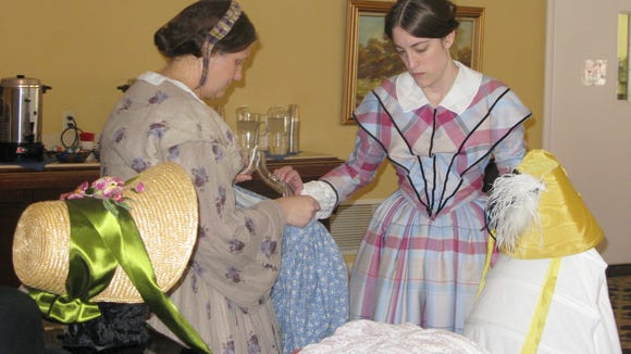 L to r: Malinda Byrne and Megan Barrell, of the Genesee Country Museum, wear period costumes while preparing a display of dresses and accessories.