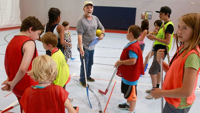 Bill Goodman, center, organizes a floor hockey game on Friday at the Aztec Boys and Girls Club. The organization has seen enrollment in its summer program increase by 20 percent at the same time that it is receiving less funding from agencies like San Juan United Way.