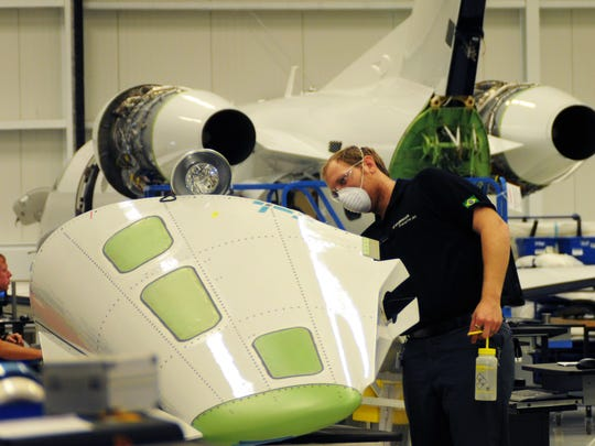 An Embraer assembly technician works on the tail cone of a Phenom 300 at Embraer Executive Jets facility at Melbourne International Airport.