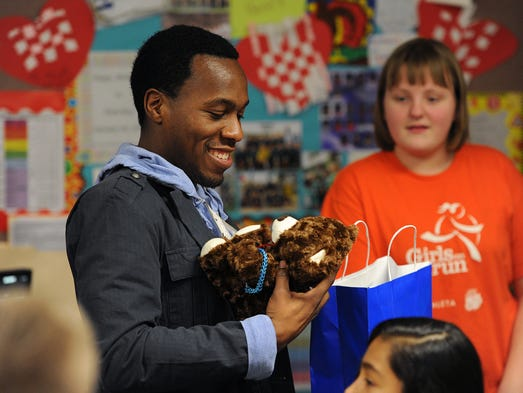 Fifth grade teacher Chris Wey holds a teddy bear his students gave him as a gift at Garden City Elementary School, Friday, January 31, 2014, in Indianapolis. Wey is leaving to join the Indy Eleven professional soccer team.
