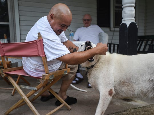 Angel Correa, known by his formal Buddhist name Rahula, laughs while playing with Huey, a five-year old American German Shepard, while relaxing with John Mulligan outside Bodhi House on Aug. 3, 2015 in Mount Joy Township.