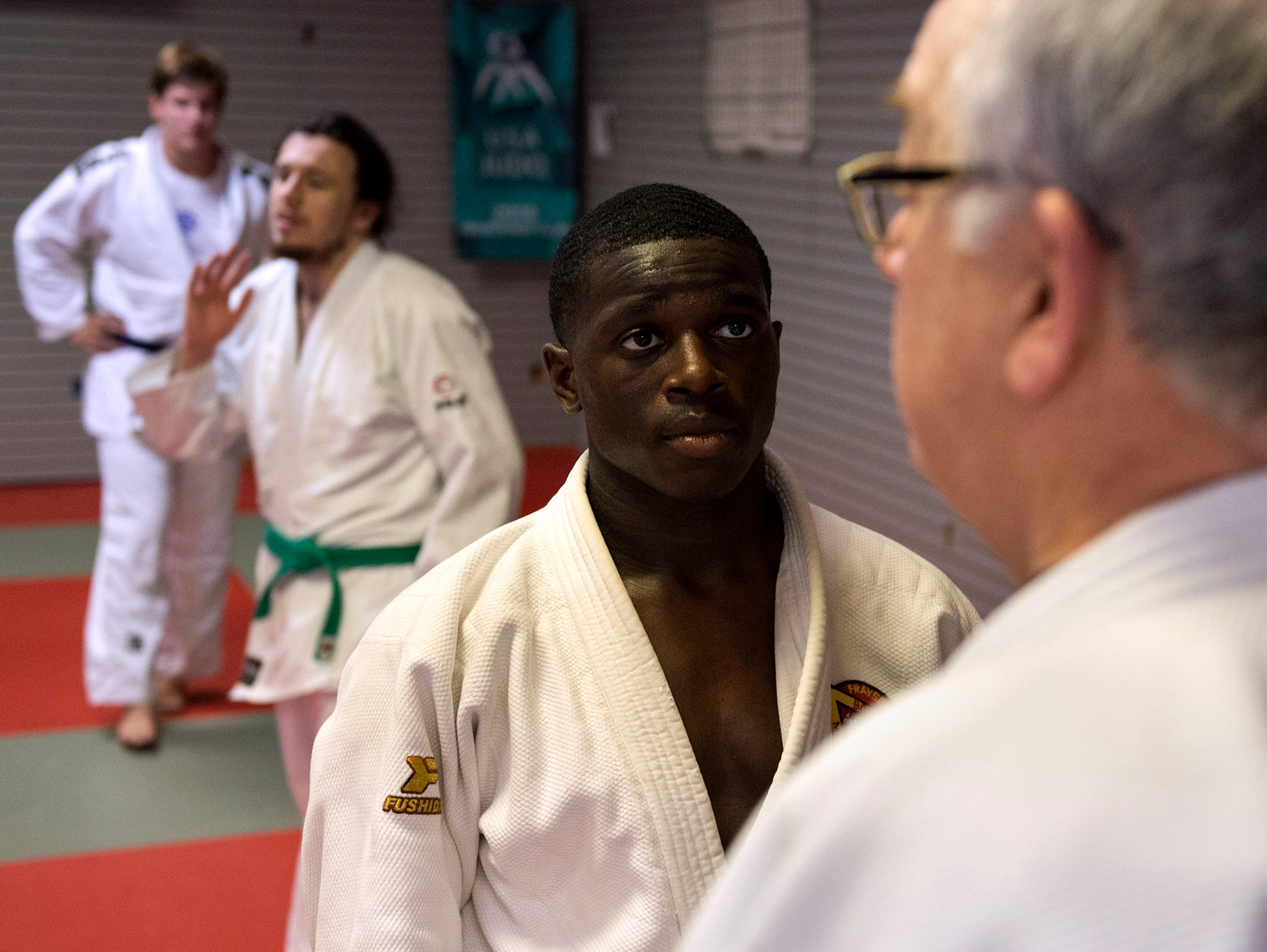 Judo coach Glen Campbell (right) teaches Darrius Isom
