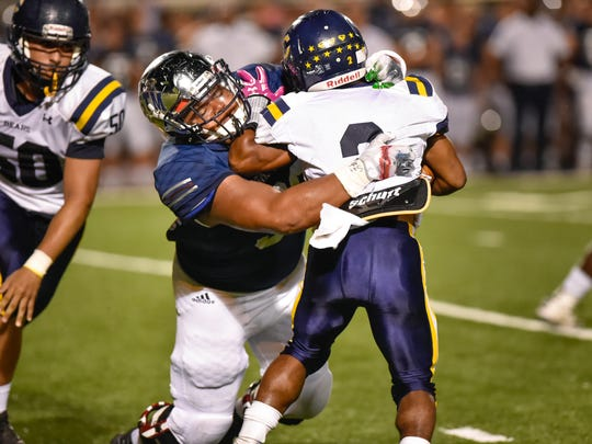 Hunter Clay makes a stop on running back Kendarius Poullard as the St Thomas More Cougars take on the Carencro Bears. October 14, 2016.