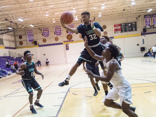Isaiah Woods gets the rebound as Lafayette High takes on New Iberia Senior High in St Martinville, La., Thursday, Dec. 29, 2016.