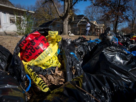 December 30, 2016 - A postal worker carries mail past discarded crime scene tape stuffed into leaf-filled trash bags in front of a house on Powell Avenue near North Holmes Street near the location where authorities found the body of Joshua Pugh on Friday morning. Pugh was pronounced dead at the scene from a gunshot wound.