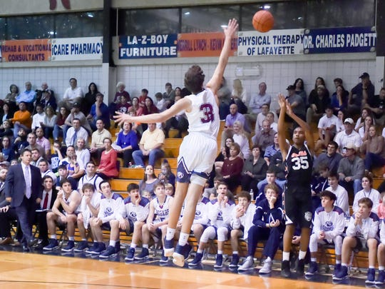 KT Thomas shoots a three pointer as the STM Cougars