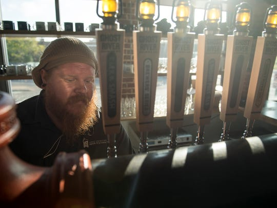 Ghost River Brewing Co. head brewer Jimmy Randall checks tap fittings in the brewery's taproom. The Memphis brewery is releasing a limited-edition porter aged in Doc.52 bourbon barrels.