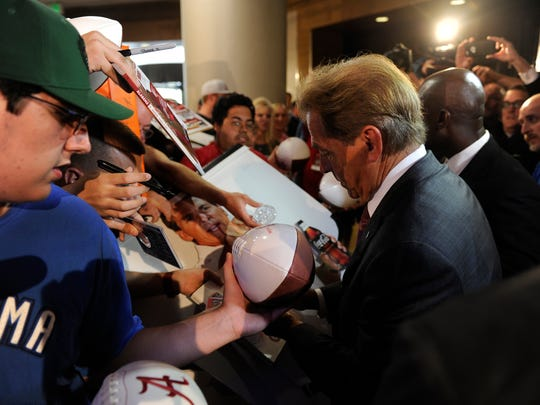 Alabama head coach Nick Saban signs autographs at SEC Media Days through a throng of reporters and fans at The Wynfrey Hotel in Hoover, Ala. on Wednesday, July 12, 2017.
