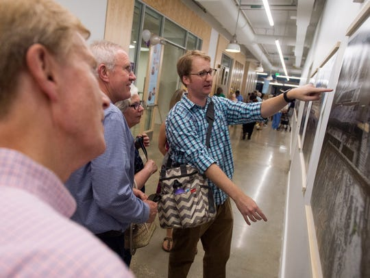 Lloyd Paul, right, an architect with Looney Ricks Kiss, explains photos showing the redevelopment of the new Crosstown Concourse building during its grand opening celebration in Memphis last August.