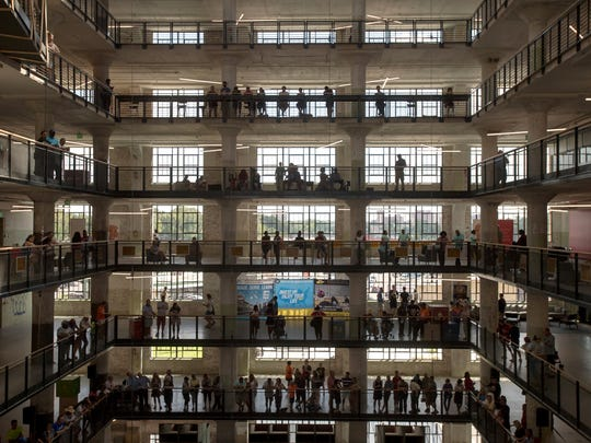 "Visitors fill central atrium during the grand opening celebration of the Crosstown Concourse building in Memphis. Built by Sears in the late 1920's, the building employed thousands of workers until it was shuttered in the mid 1990's. In 2010 work began to transform the building into a ""vertical urban village"" which which is now home to dozens of tenants including art galleries, restaurants, fitness centers, education organizations, health care facilities, places of worship, banks as well as residential living spaces."