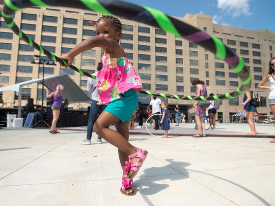 Skye Adams, 2, plays with a hula hoop during the grand