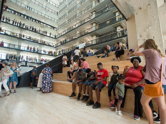 "Visitors fill the central atrium during the grand opening celebration of the Crosstown Concourse building in Memphis. Built by Sears in the late 1920's, the building employed thousands of workers until it was shuttered in the mid 1990's. In 2010 work began to transform the building into a ""vertical urban village"" which which is now home to dozens of tenants including art galleries, restaurants, fitness centers, education organizations, health care facilities, places of worship, banks as well as residential living spaces."