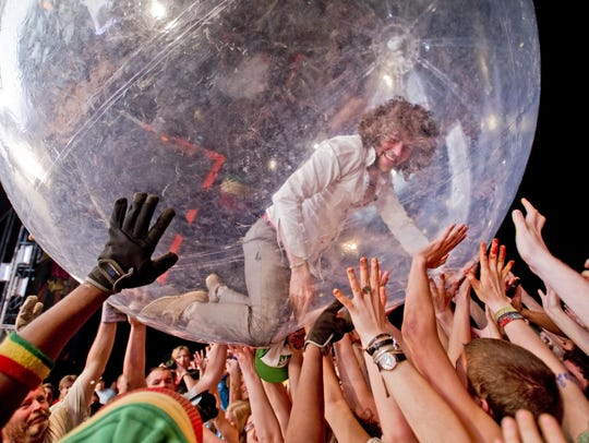 Wayne Coyne of The Flaming Lips rides across a crowd of fans in a plastic bubble while performing. See the band in August at Bellwether Music Festival.