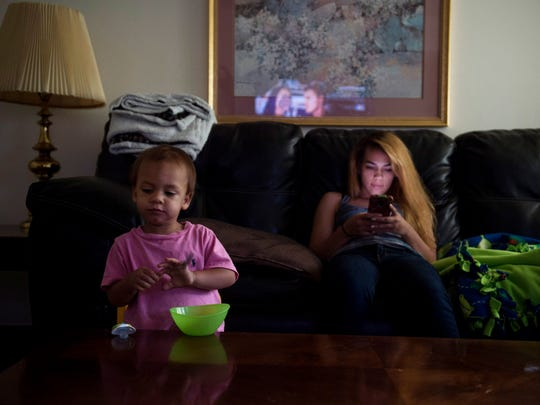"Brooke relaxes at home after her family lunch while Vincent eats a snack on Sept. 17, 2017. On weekends, she spends most of her time with her son rather than socializing with friends. ""I tell her, you know, you really can't go all out and be a teenager because you've still got your son to worry about,"" said her father Michael Winfield. ""If you get in trouble or you get hurt, you know, its going to reflect back on you being a mom, and you know, your son."""