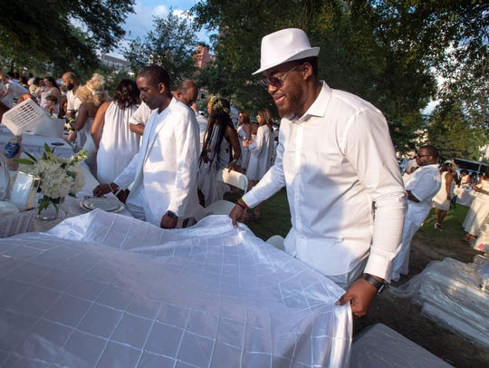 August 4, 2018 - Morris Robinson spreads a table cloth