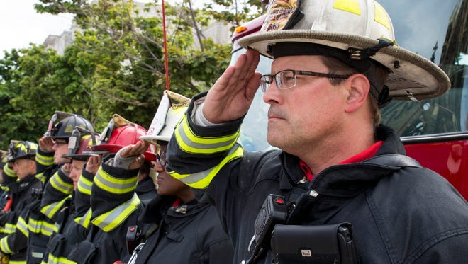 Recently appointed Milwaukee Fire Department Chief Aaron Lipski salutes with fellow firefighters in 2018.