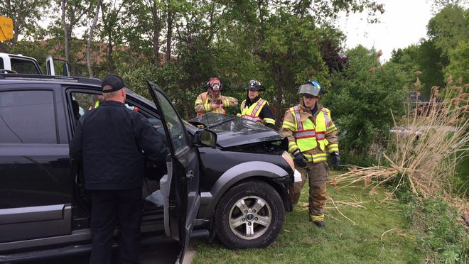 A vehicle that struck a telephone pole in a three-car crash Wednesday afternoon is pulled out of brush behind A Do 4 U Salon and Tanning on University Avenue in Green Bay.