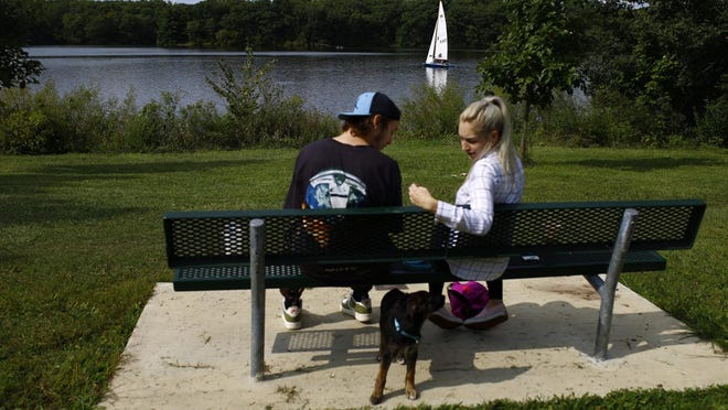 Joe Parsons and Hannah Winterland of Rockford picnic with their dog Appa as a boat sails on Pierce Lake at Rock Cut State Park on Thursday in Loves Park. Rock Cut is one of the region's biggest attractions for visitors, drawing more than 1.1 million people last year, according to the Rockford Area Convention & Visitors Bureau.