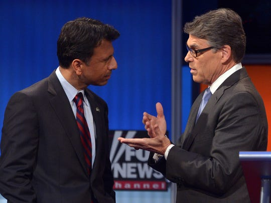 "Louisiana Gov. Bobby Jindal listens to former Texas governor Rick Perry during the ""happy hour"" presidential primary debate on Aug. 6, 2015, at the Quicken Loans Arena in Cleveland."