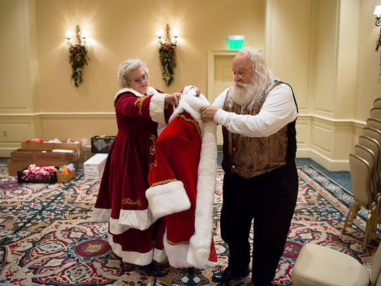 Mrs. Claus, Deborah Reed, helps her husband Santa Claus, Dennis, into his coat just before the start of a Gingerbread House Tea at The Inn on the Biltmore Estate.