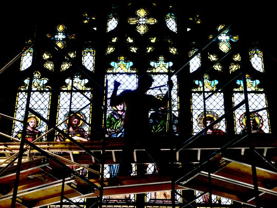 Oliver Fourneir, of Willet Hauser Architectural Glass climbs a scaffolding inside of Trinity Episcopal Church downtown to work on restoring a large stained glass window above where the organ normally sits on Tuesday, Aug. 30, 2016. The windows were being cleaned, strengthened and having any warping or places in need of new lead repaired.