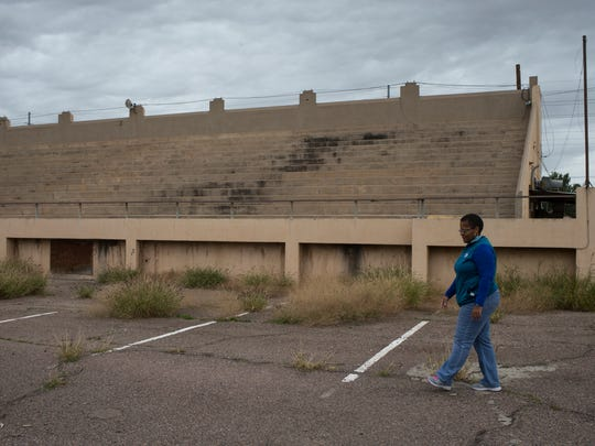 Board President Princess Crump walks past the old football stadium at the George Washington Carver Museum and Cultural Center in Phoenix. The Arizona Community Foundation is working with alumni and community members to raise the profile of their efforts, which include seeking a place on Phoenix's historic register.