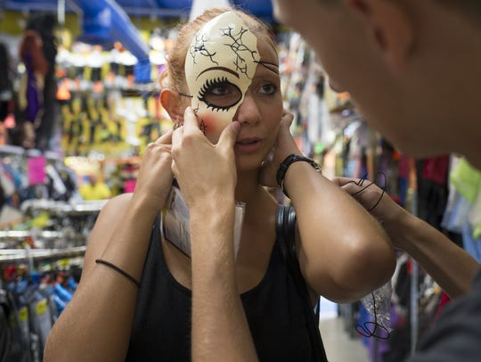 Sondra Gross tries on a mask with the help of her friend,