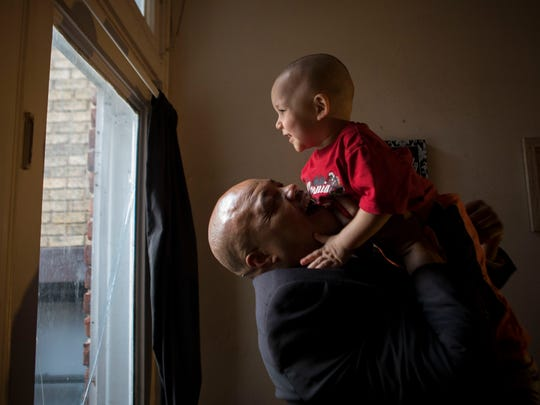 Mon., Jan. 22, 2018: Reggie Hughes of Covington plays with his son, Jayceon. Jayceon was born with neonatal abstinence syndrome, dependent on opioids because his mom had heroin addiction. He didn't have much withdrawal, Hughes said. But he did develop a head tilt. With treatment, Children's Hospital Medical Center found that this can be corrected. Researchers say that Jayceon, who has been receiving physical therapy in the Children's clinic, is a success.