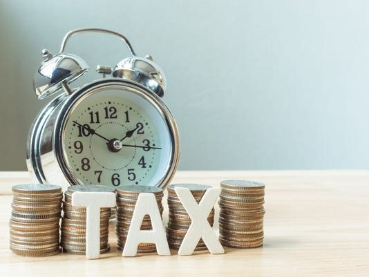 Concept tax time and alarm clock with coins stack