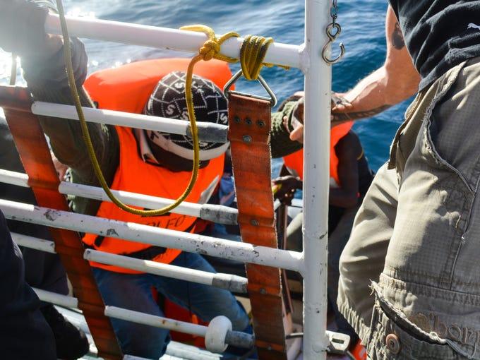 Rescuers on Minden assist Sali Baldel, 19, into a raft