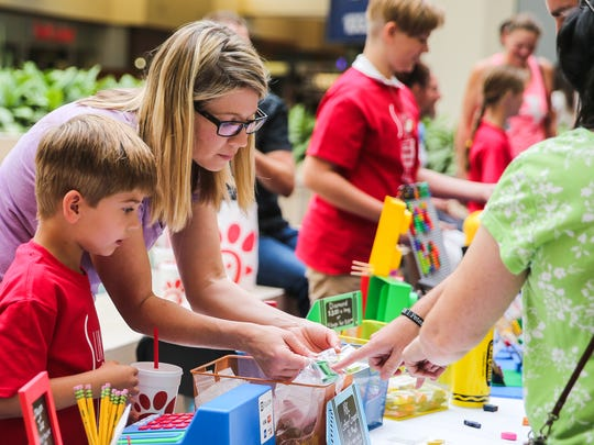 Liam Peters, 6, gets help showing his canyon creations to customers during the Kids, Inc. Business Showcase Saturday, July 28, 2018, at the Sunset Mall.