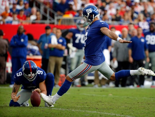 Punter Brad Wing (9) holds the ball for Giants kicker