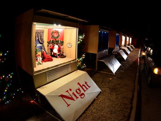 "Cars file past the ""Twas the Night Before Christmas"" display of dioramas depicting the holiday poem in the Santa Rita area."