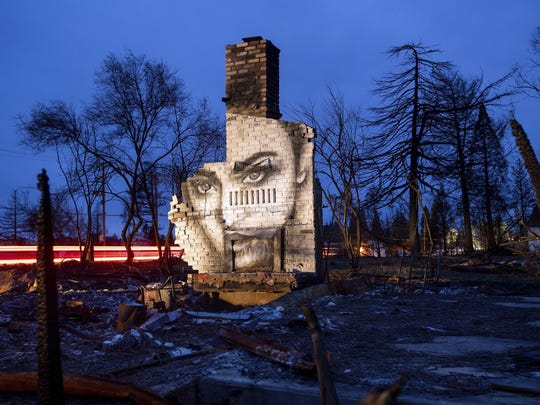 In this Feb. 8, 2019, photo, a mural by artist Shane Grammer adorns the chimney of a residence leveled by the Camp Fire in Paradise, Calif. Grammer says he painted murals throughout the fire-ravaged town to convey hope in the midst of destruction.