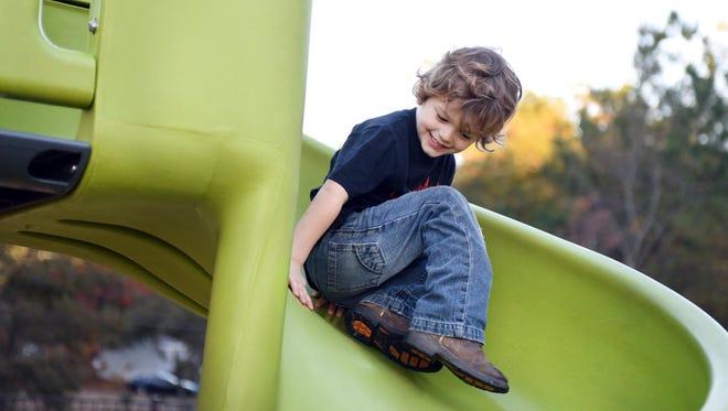 Wyatt Self slides down the playground equipment in Lamar County's Backstrom Park.