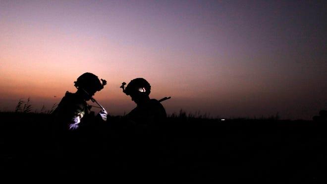 U.S. Army soldiers confer during a patrol north of Baghdad in 2011.