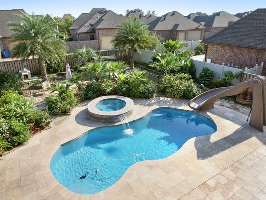 The gorgeous pool is surrounded by lush landscaping.
