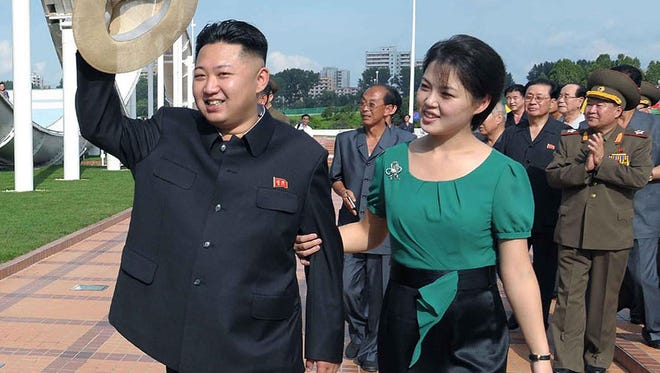 In this undated file photo released by North Korea's official Korean Central News Agency (KCNA) via the Korea News Service (KNS) on July 26, 2012  shows North Korean leader Kim Jong-Un (L), accompanied by his wife Ri Sol-Ju (R), visiting a wading pool at the Rungna People's Pleasure Ground in Pyongyang.