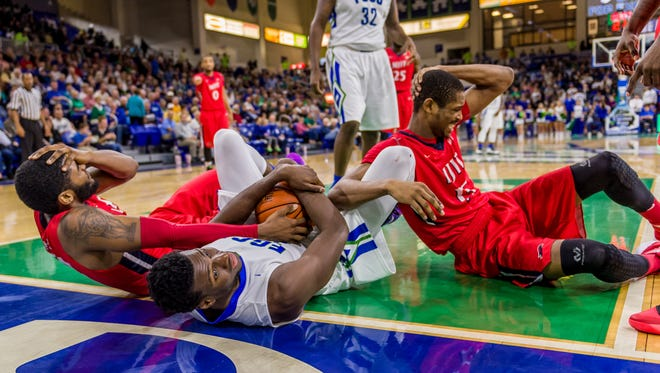 FGCU's Marc-Eddy Norelia corrals a loose ball between two NJIT players this season in Alico Arena.
