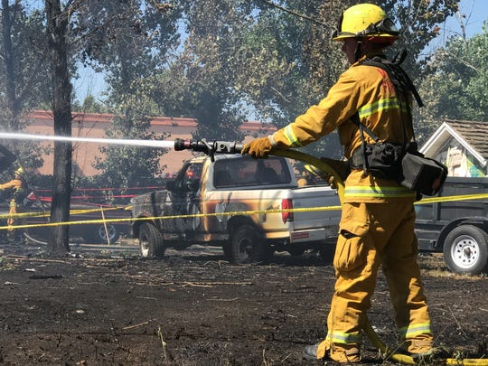 Firefighters with CAL FIRE, Tulare County and Visalia fire departments are working to contain a grass fire that spread to homes near Chinowth Street.